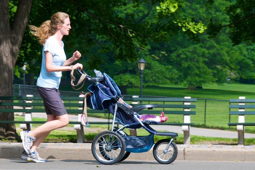 молодая мама бегает с коляской
